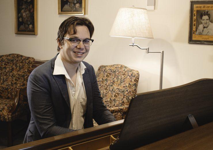 Joshua Cossette sitting at piano