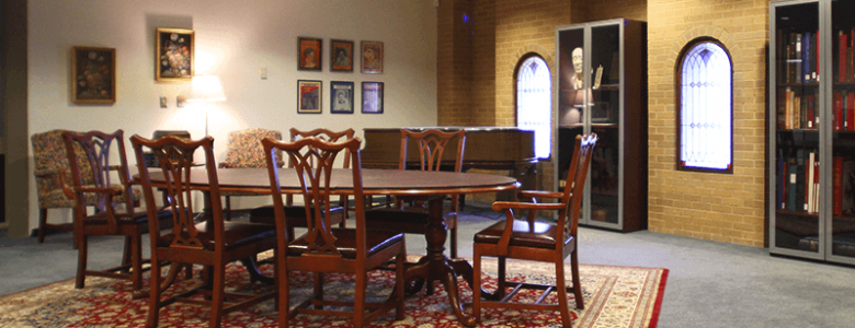 Image of the reading room with a carpet and wood table and chairs. Art is hanging on the walls.