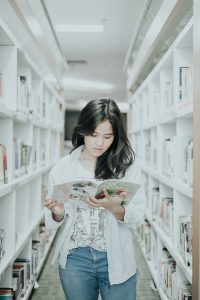 A woman reading a book on a pathway between the book shelf