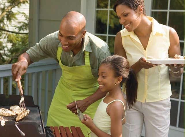 An African American father, mother, and young daughter barbecuing in the backyard.