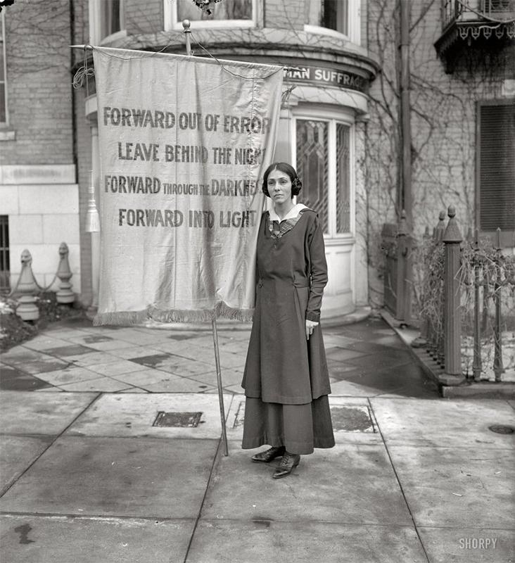 Woman holding banner at Inez Milholland memorial.
