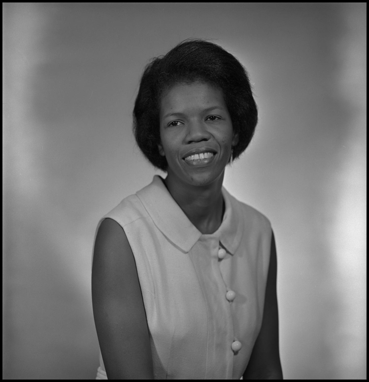 black and white photograph of an African-American women from the waist up, with a sleeveless button-down top