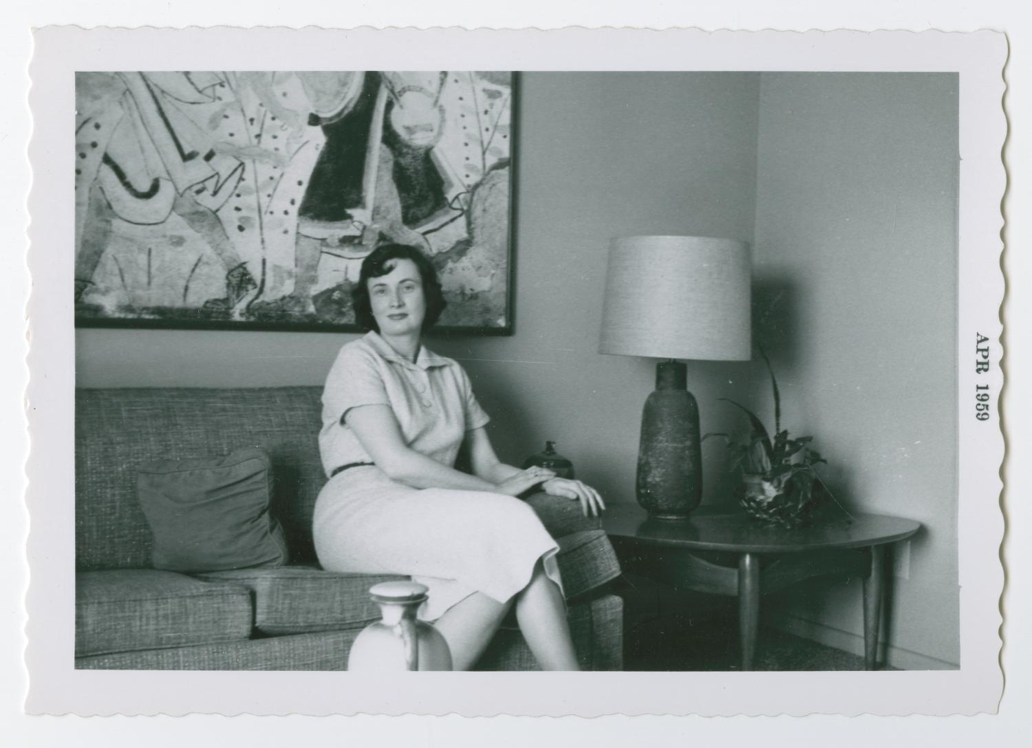 black and white photograph of woman sitting with legs crossed on a couch. She wears a white dress, and a table with lamp is beside her with a geometric painting hanging on the wall behind her.