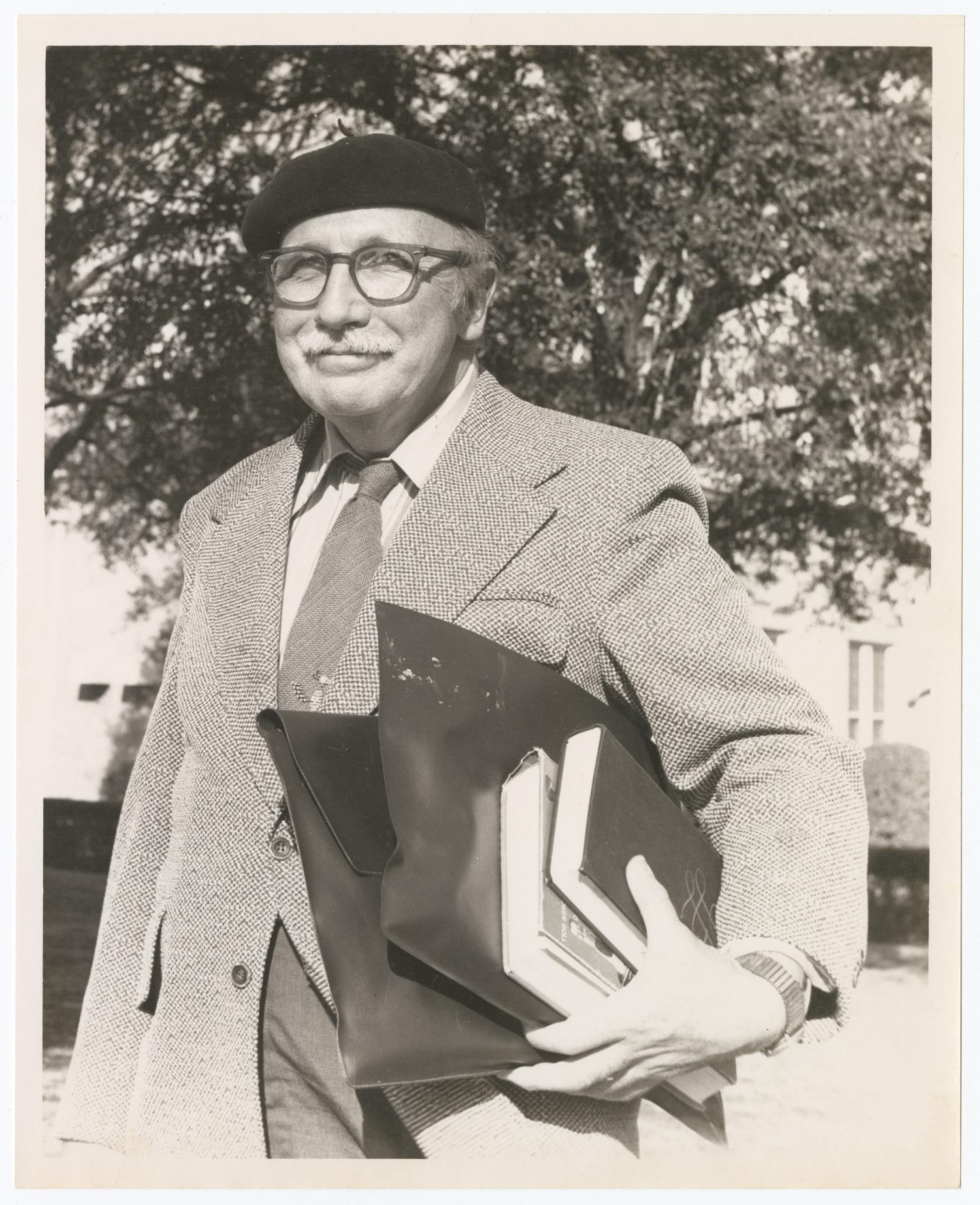 black and white photo of an older man from waist up standing outside holding books and folders in one hand. He wears a blazer, tie, large glasses, and a black beret.