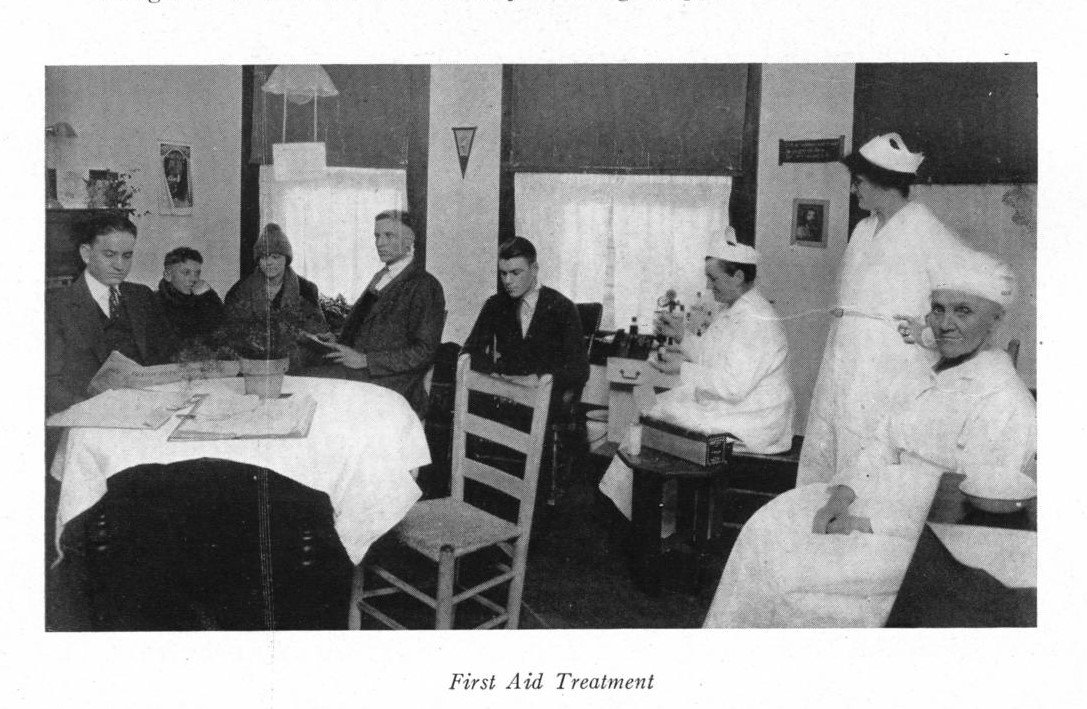 black and white photo of men sitting behind a table wearing suits to the left, with nurses in white dresses and hats to the right