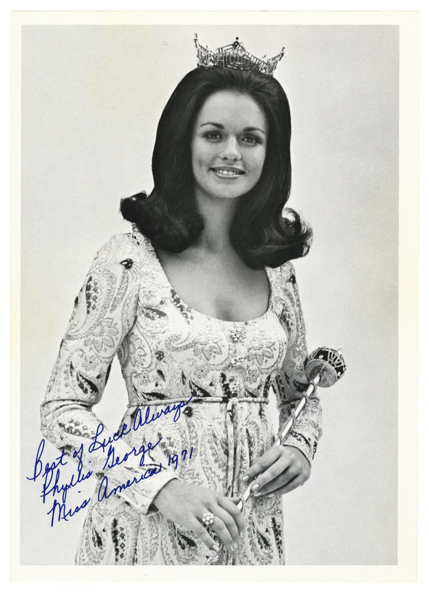 "black and white photo of woman wearing a floral dress and a tiara, holding a scepter. it is signed on the bottom left in blue ink reading ""Best of luck always, Phyllis George, Miss American 1971"