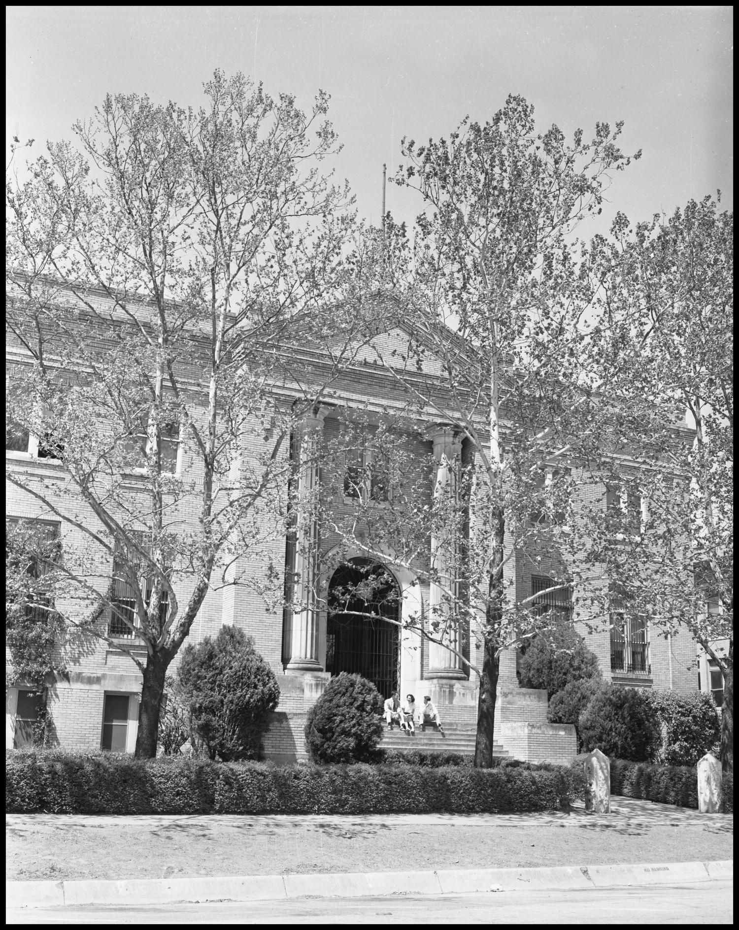 black and white photograph of building obscured by large leafless trees. The building has a rectangular facade with many windows, and the entrance at center has a large arched doorway with two large columns on either side, and a staircase in front.