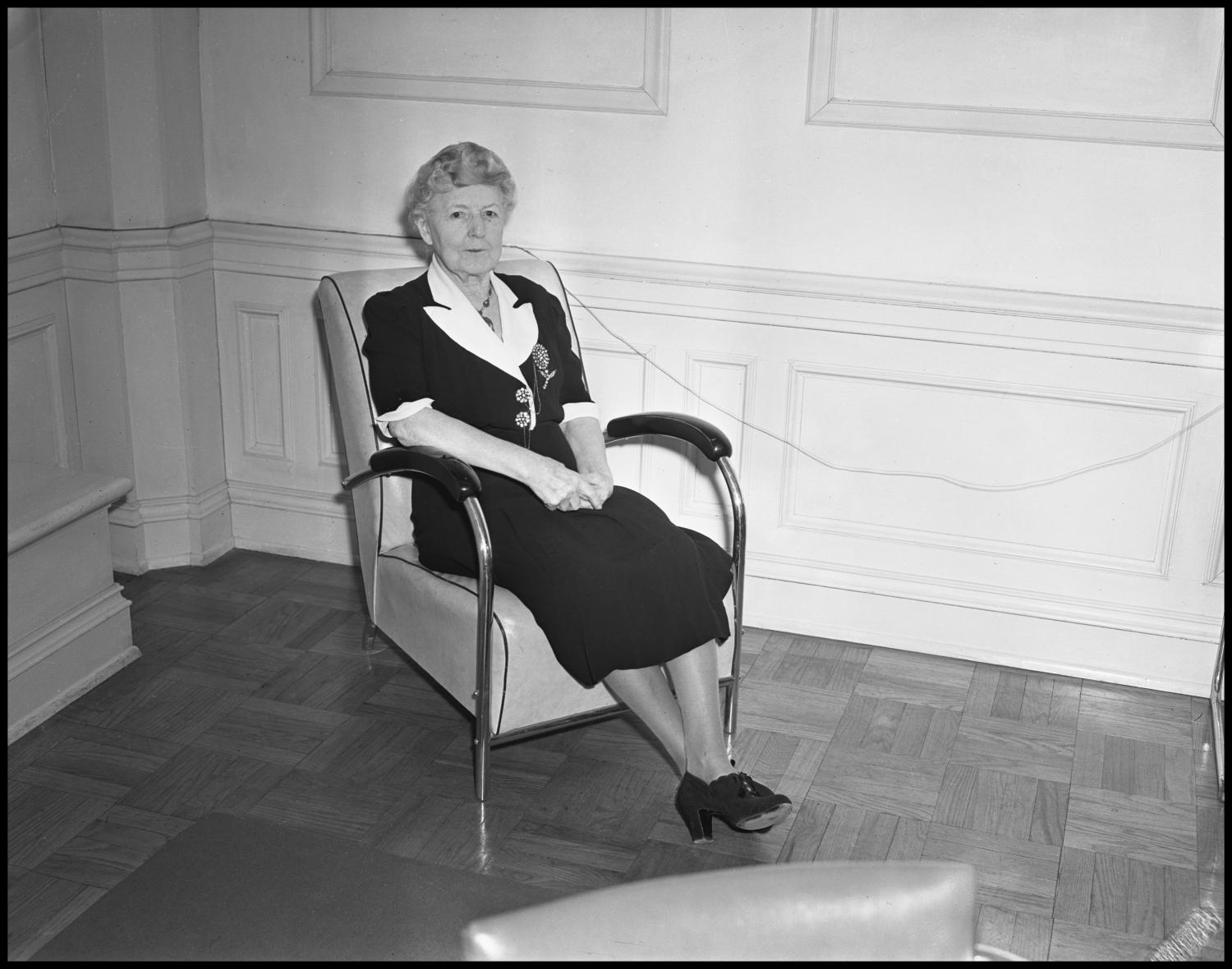 black and white photograph of older woman sitting in a chair. she wears a black dress with white lapels and two buttons on the front. she looks at the camera with his hands clasped in her lap.