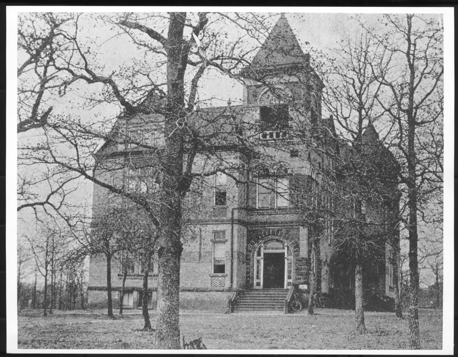 Black and white photo of brick building with small staircase leading to arched front door on the right. building has many windows and a small tower above main doorway with pyramid shaped roof. many leafless trees stand in front of building partially obscuring it.