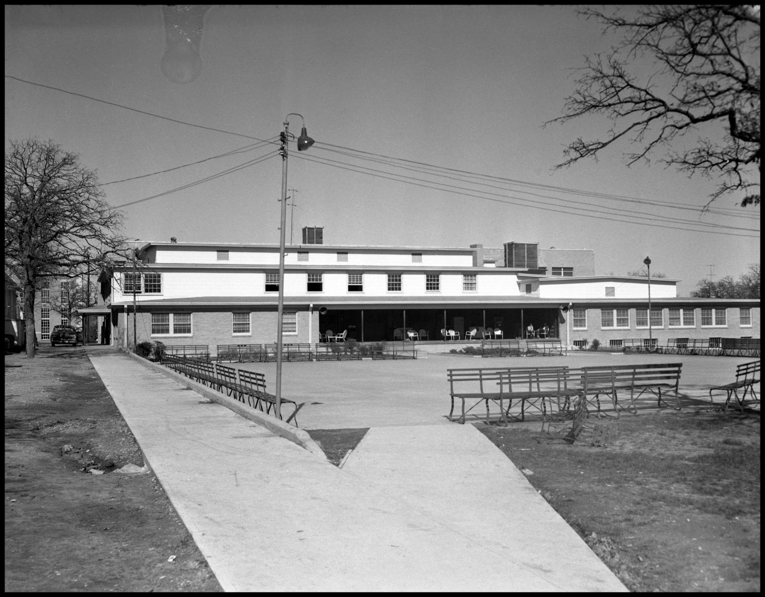 Black and white photo of a wide three story building with a large empty concrete slab in front. Around the edges of the concrete slab are benches, and a telephone pole stands at the corner closest to the camera.
