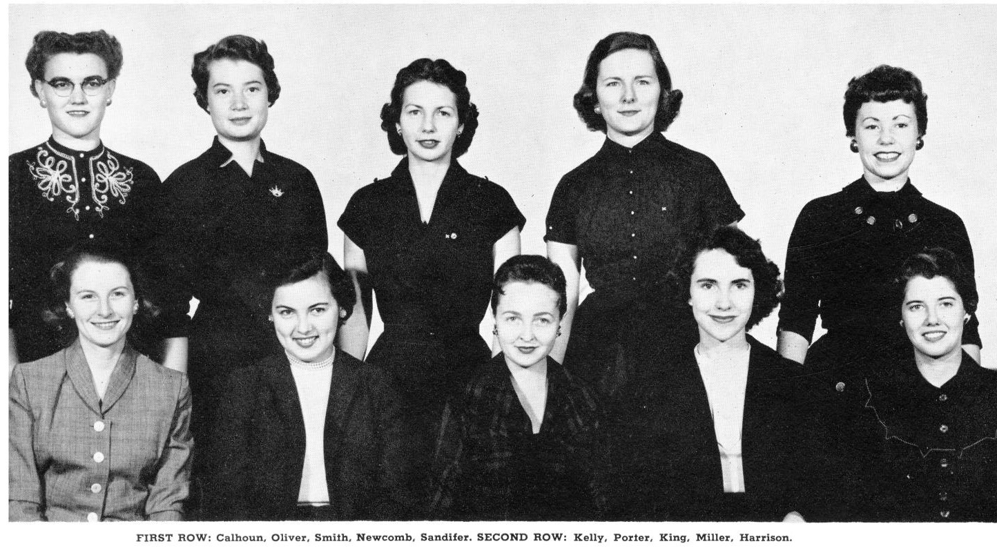 Black and white photo of a group of ten women in two rows. The front row sits while the back row stands. Women are dressed in dark clothing with 1950s clothing and hair styles.
