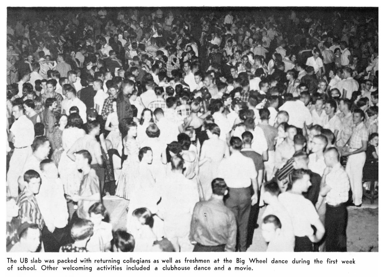 Black and white photo of a large crowd of people all talking or dancing in small groups or pairs.