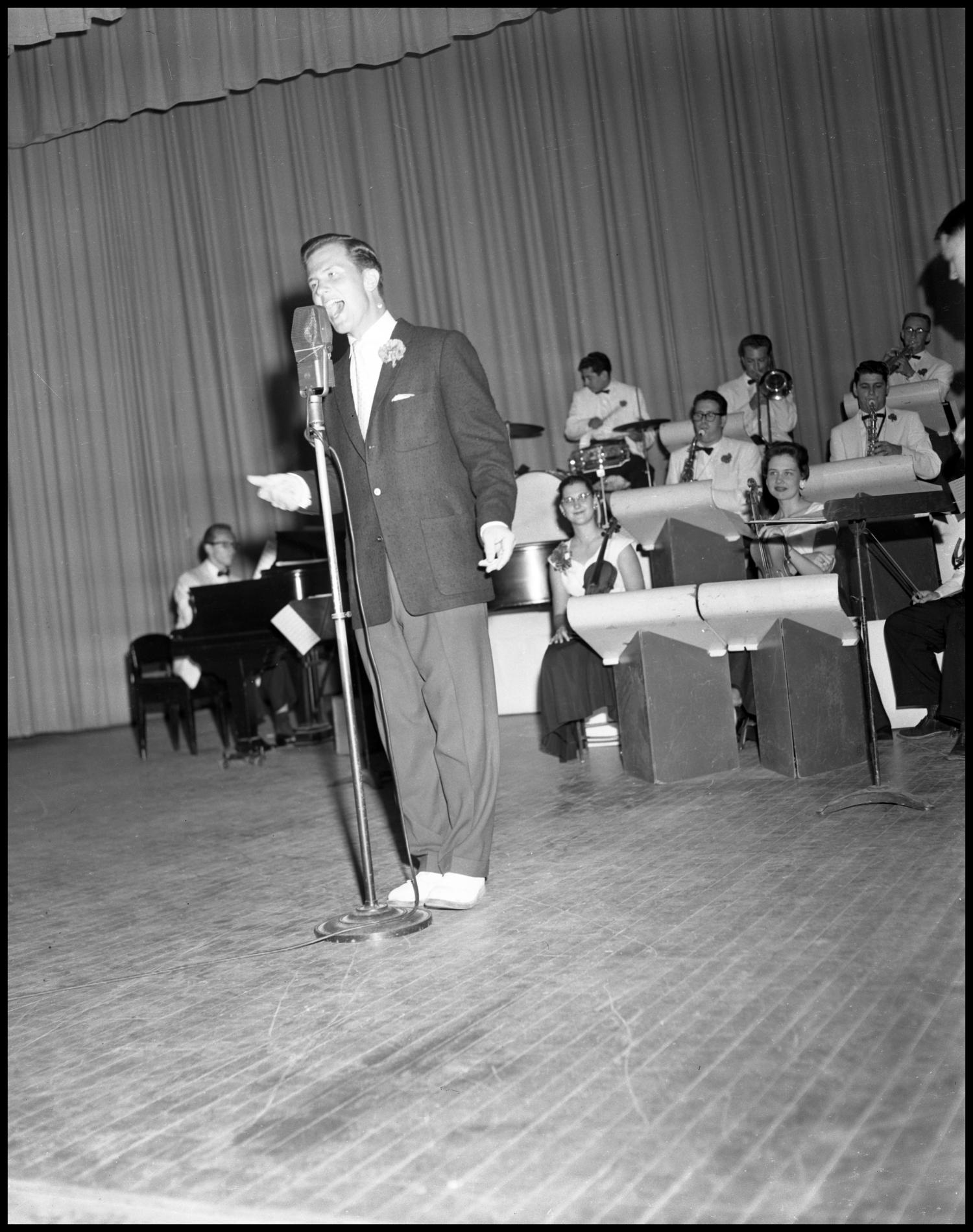 Black and white photograph of a white man in a suit singing into a microphone with a big band behind him.