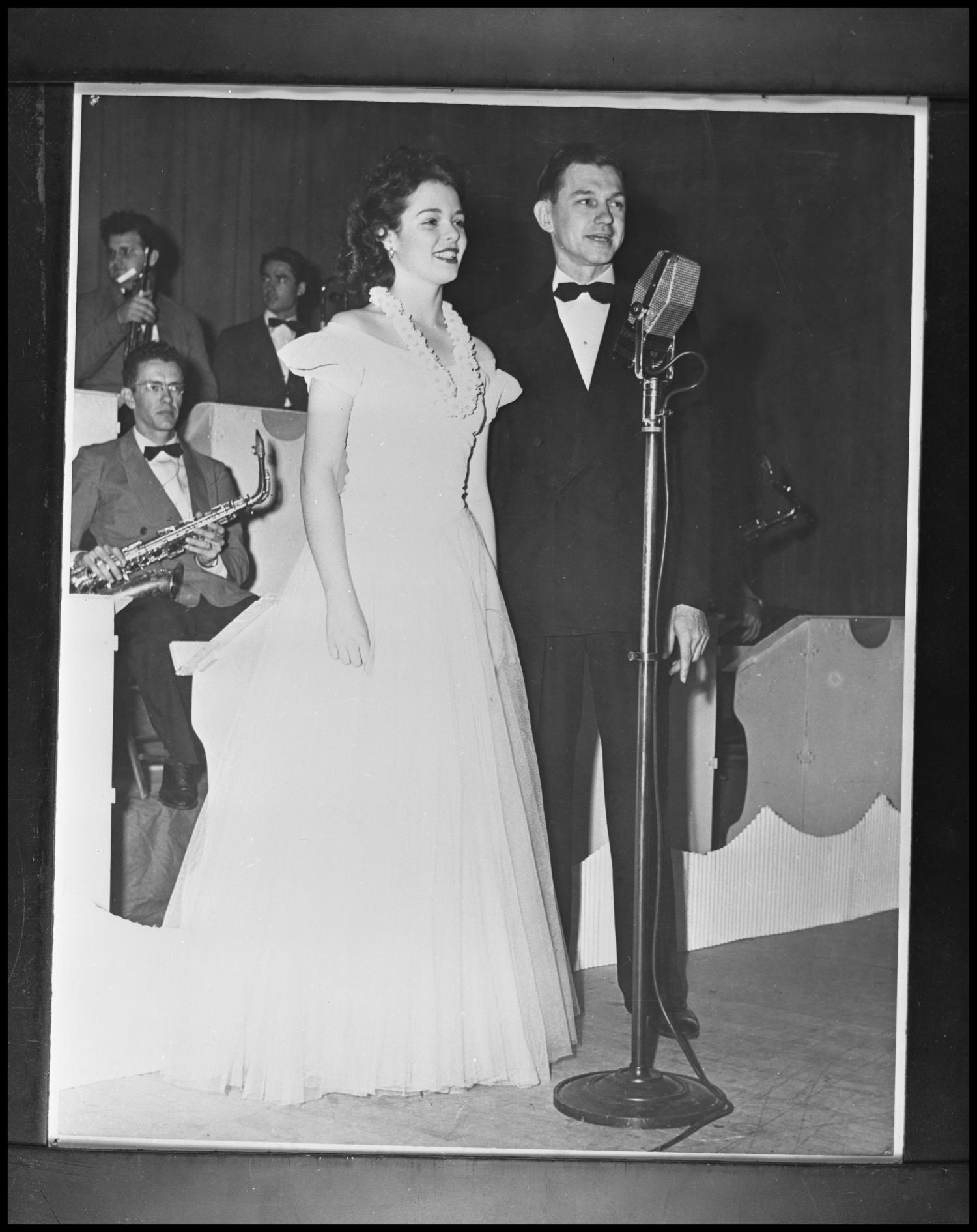 Black and white photo of a white man and woman standing in front of a microphone. She wears a floor length white dress and he wears a tuxedo. Members of a big band can be seen behind them.