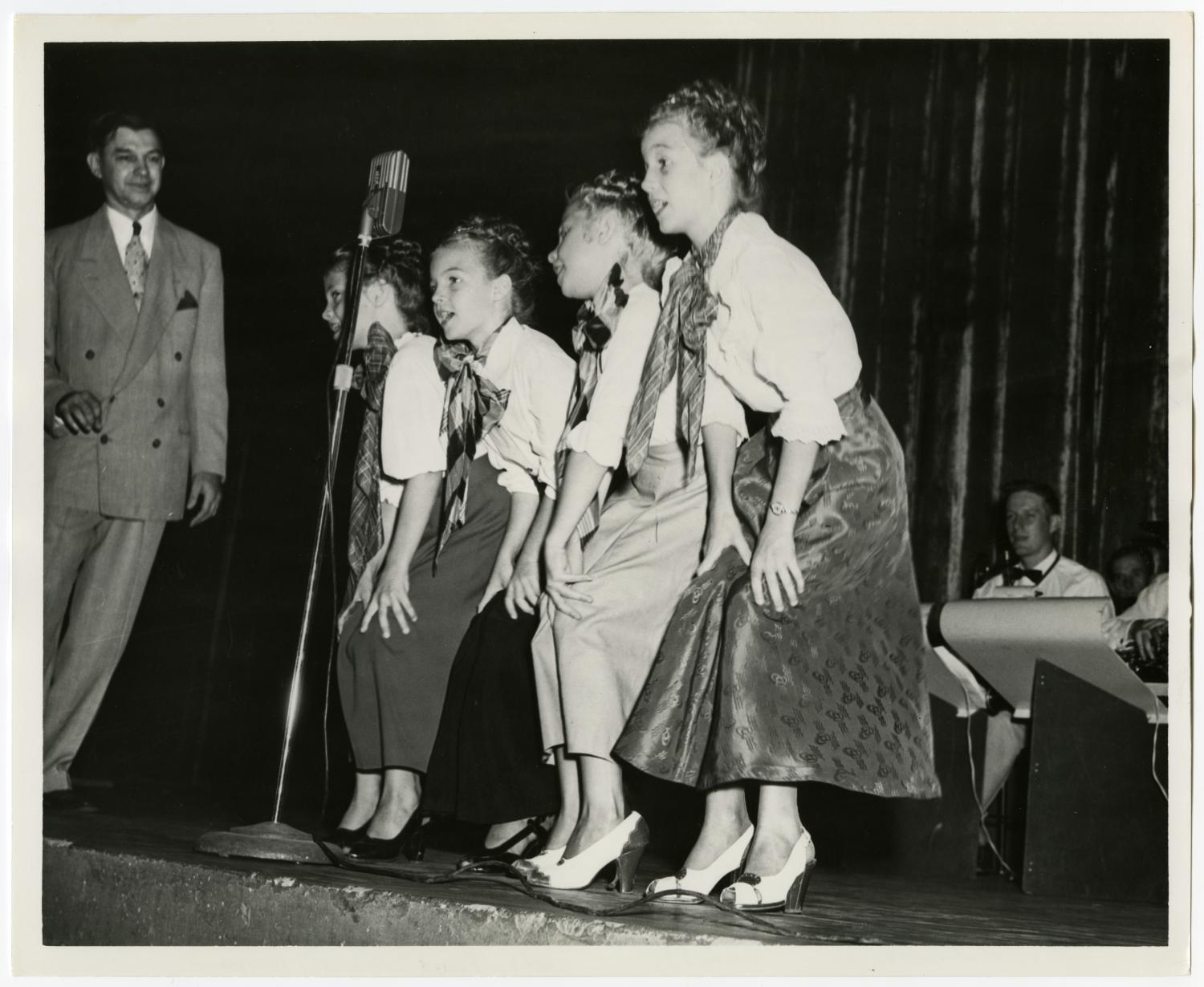 Black and white photo of four young girls dressed in long skirts and heels, singing into a single microphone on a stand. Members of a band can be seen behind them, with a man standing to the far left in a suit on stage.