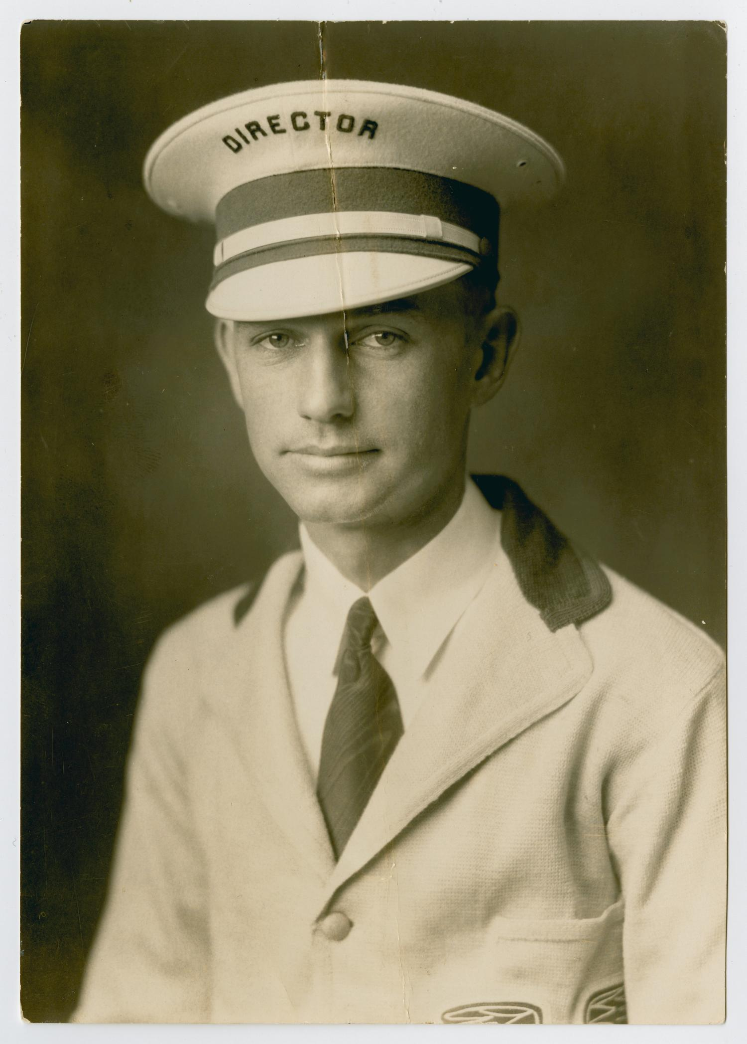 Black and white bust length portrait of a white man wearing a light colored suit jacket over a collared shirt and tie. He wears a light colored military style hat with brim in front, and across the top it reads 'Director.'