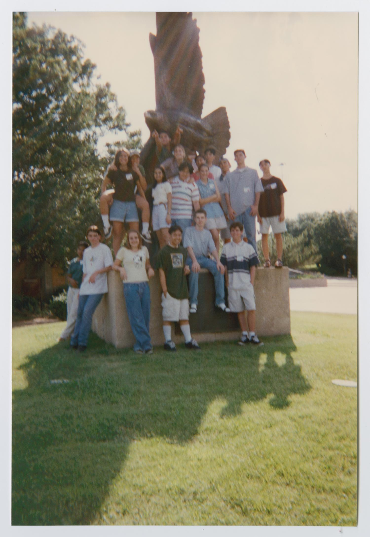 Group of students standing on the ground and on the raised base of a statue outdoors. The statue above them is of a flying eagle.