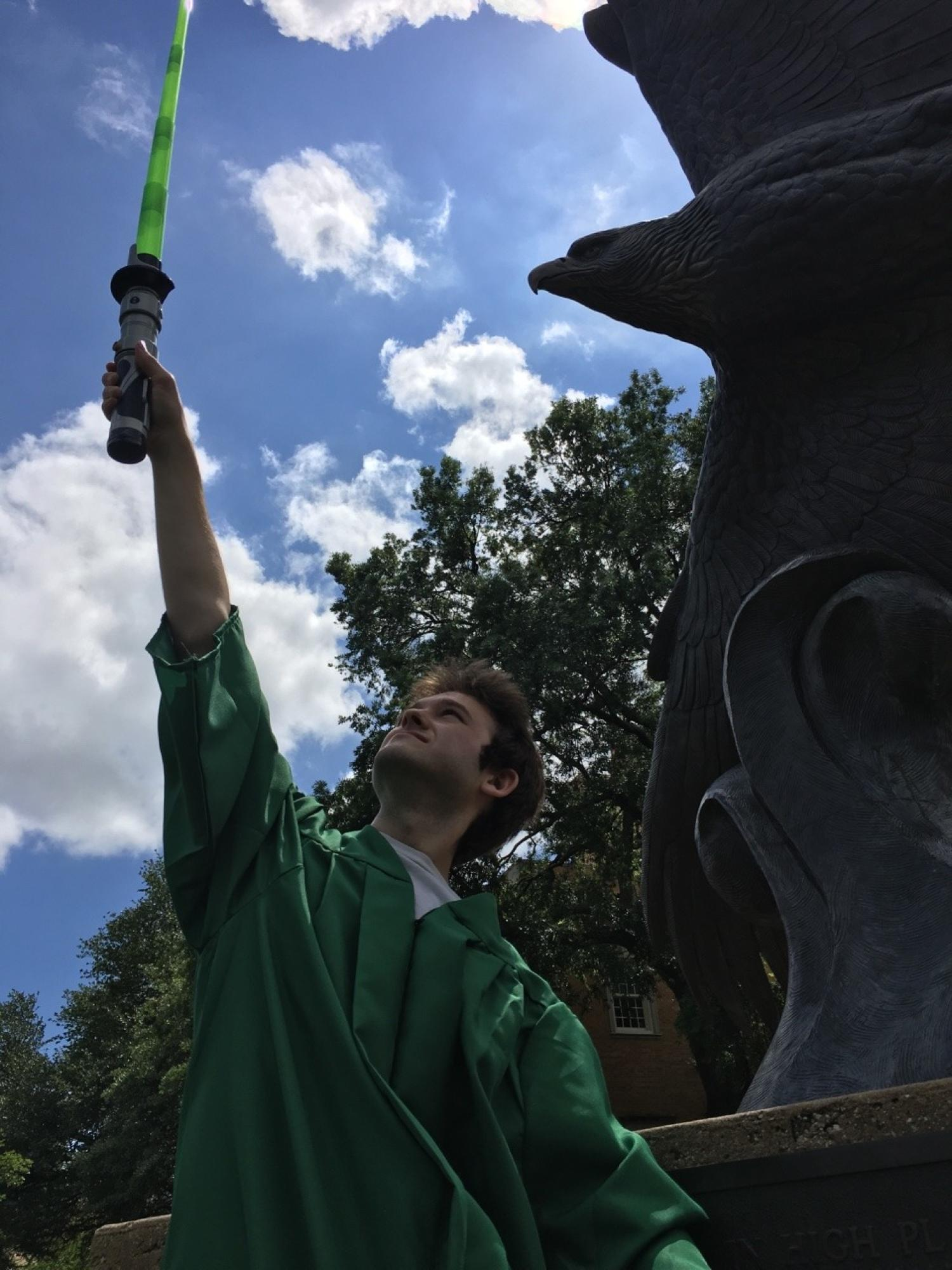 Man in green graduation robe holds a toy lightsaber in the air outdoors. Part of a large flying eagle statue is next to him. Both look upwards.
