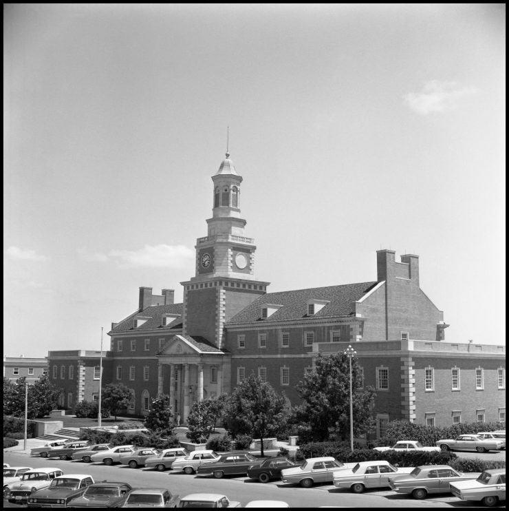 Black and white photo of brick building with large clock tower at center, and cars parked in front.