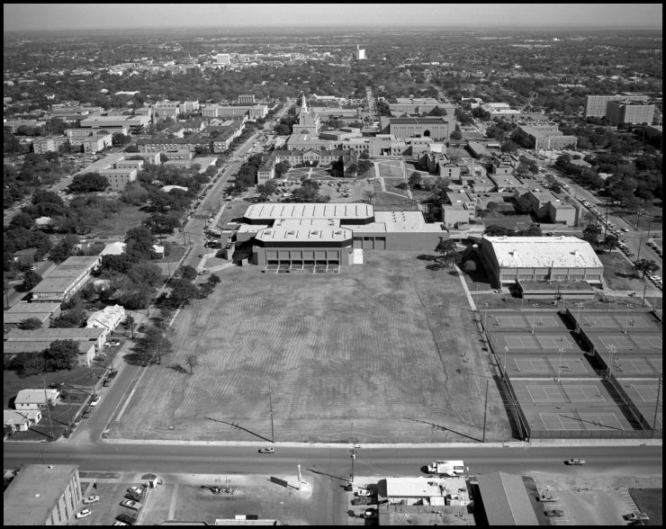 Black and white aerial photograph with a large open lawn in the foreground, tennis courts to its right, and two large buildings just behind. Other buildings, walkways and streets are visible further back.