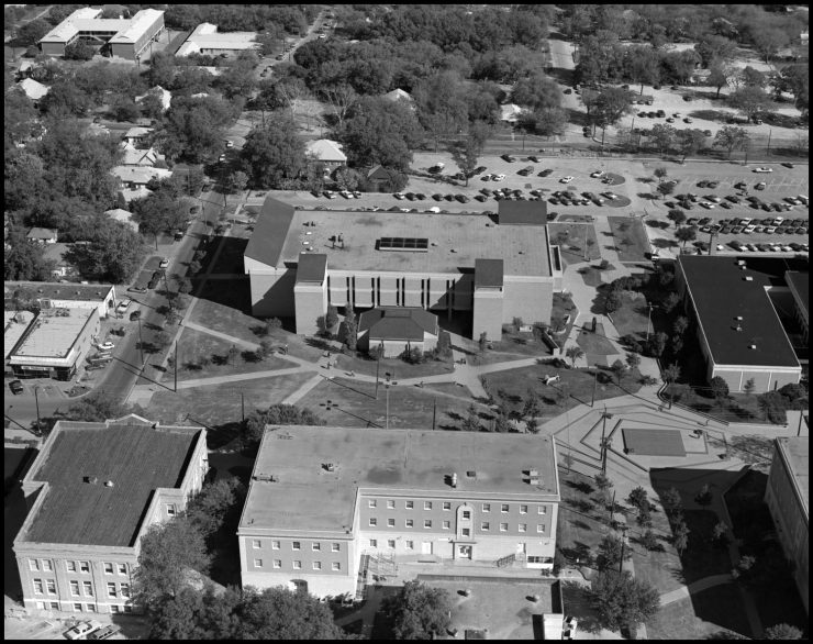 Black and white aerial photograph of three full buildings, and edges of surrounding buildings. Pathways run between buildings creating geometric lawns. and a parking lot is seen in the background.