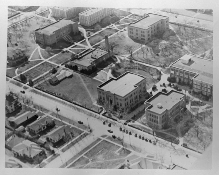 Black and white photo of aerial view of various buildings with large areas of lawn and walkways between them.