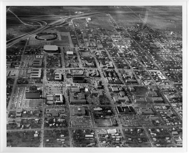 Black and white aerial photograph of buildings and streets. A highway and open land are visible at top left, with a football field just below.