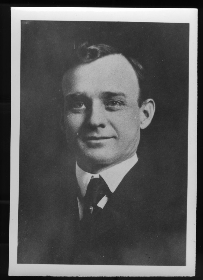 Black and white portrait of a white man in a dark suit and tie.