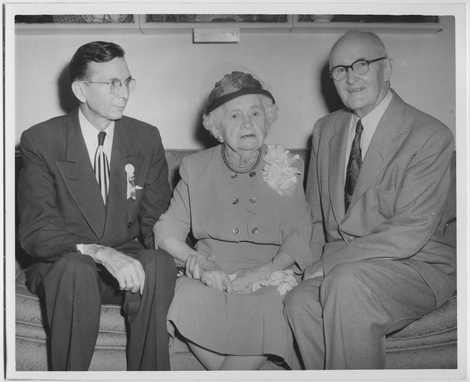 Black and white photo of an elderly woman seated between two men in suits. She wears and dress and hat.