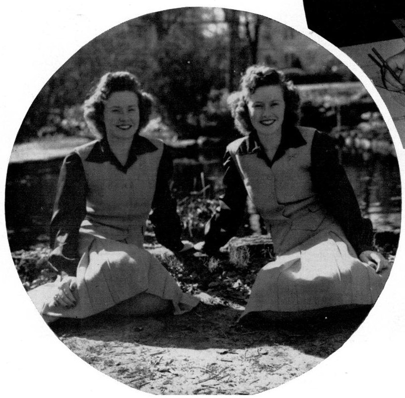 Two women, identical twins, sit on the ground outside holding hands. They wear identical dresses.