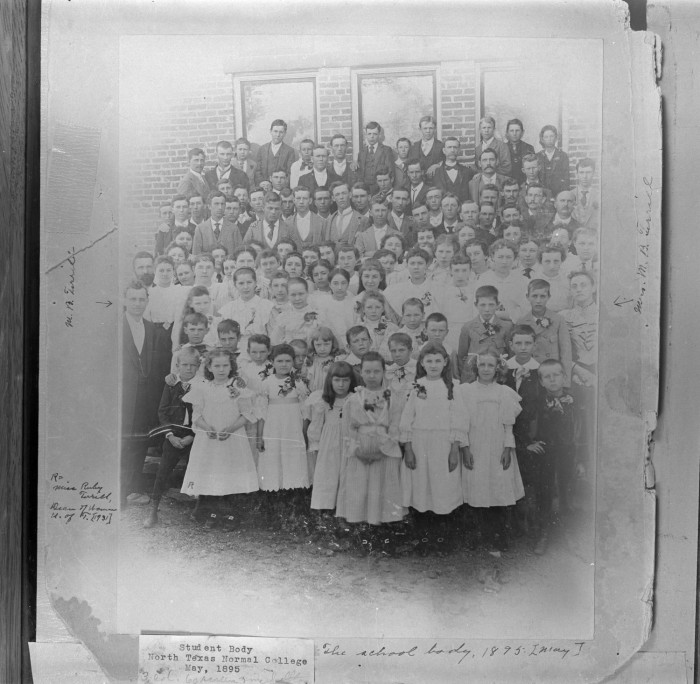 Black and white photograph of a large group of children posing for a class photo. The girls towards the front wear mostly white dresses, while boys towards the back wear suits.