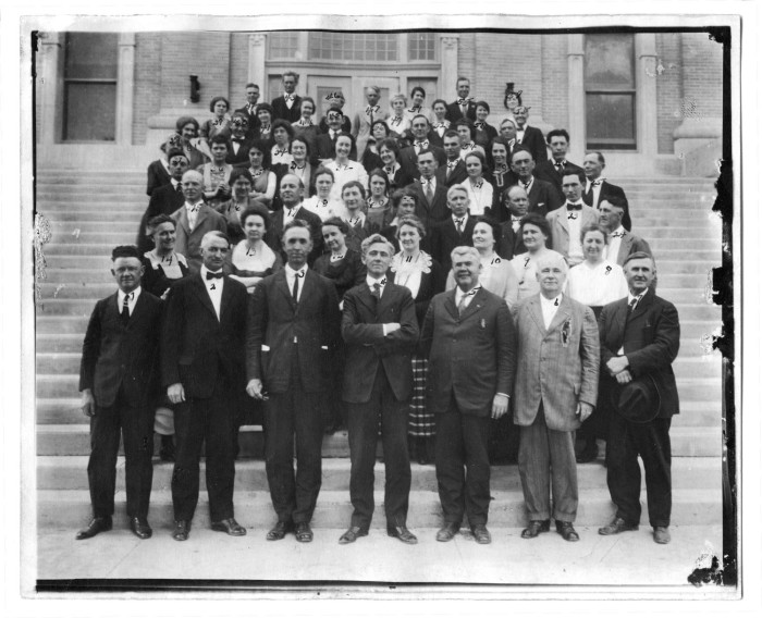 Black and white photograph of a group of people standing on steps. The men wear suits and women wear dresses.