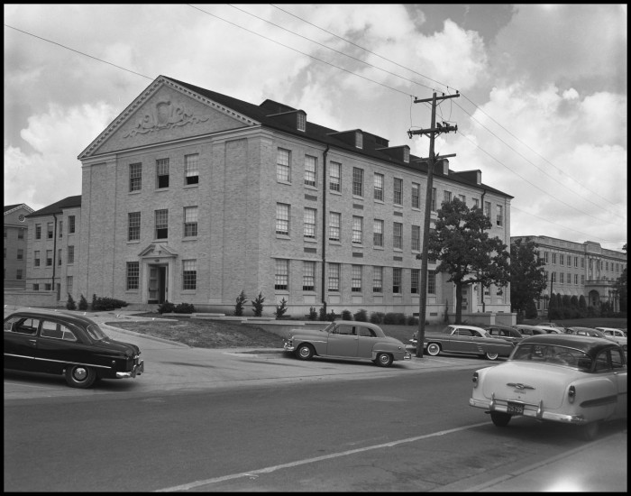 Black and white photograph of a three story brick building with many window. A relief sculpture of intertwined snakes is at the top of one end of the building.