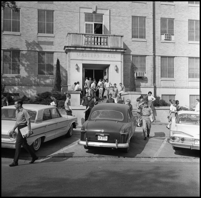 Black and white photo of people exiting a building with cars parked in front. Above the door, text reads Masters Hall.