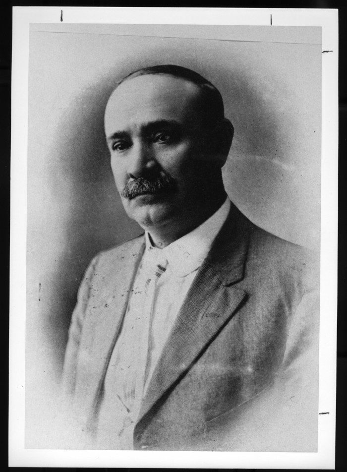 Black and white photo of older balding man, with moustache, wearing a suit and tie.