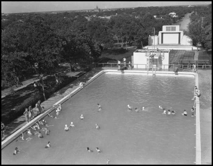 Aerial black and white photograph of a large rectangular swimming pool with people scatter throughout.