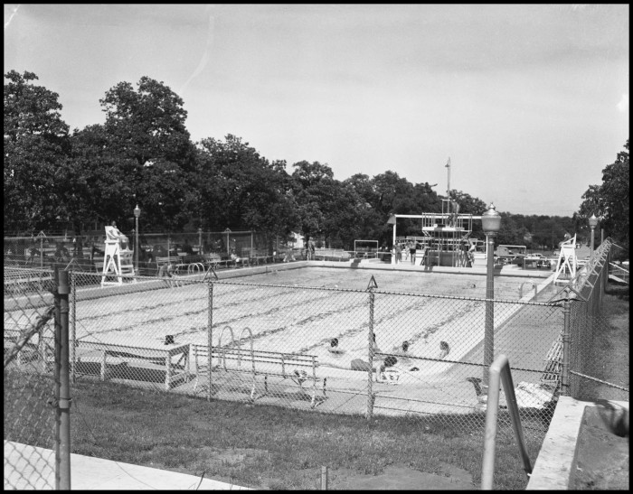 Black and white photograph of an outdoor swimming pool with a lifeguard stand and a group of people in the nearest corner of the pool.