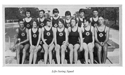 Black and white photo of men and women posing for photo in two rows. They are in front of an outdoor swimming pool, and they all wear black leotard like swimsuits with a white circle on the chest with a cross inside.
