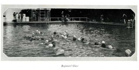 Black and white photograph of two lines of people swimming in opposite directions in a swimming pool.
