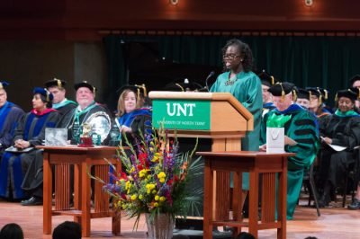 Color photograph of a student wearing graduation robe speaking at a wooden podium. Rows of people sit behind her on stage wearing various types of graduation gowns and caps.