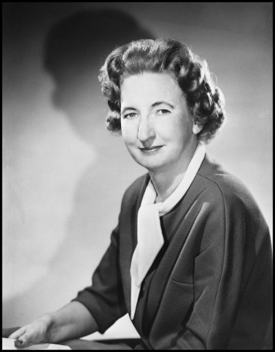 Black and white portrait photograph of a woman with short hair in tight curls, wearing a dark blazer with white short scarf.