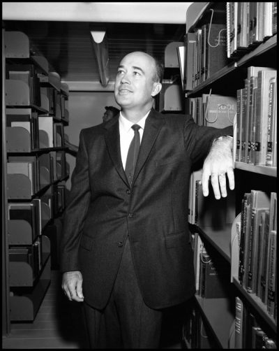 Black and white photograph of a balding man standing between two sets of metal book shelves. He leans his elbow on a shelf and looks up and to his right.