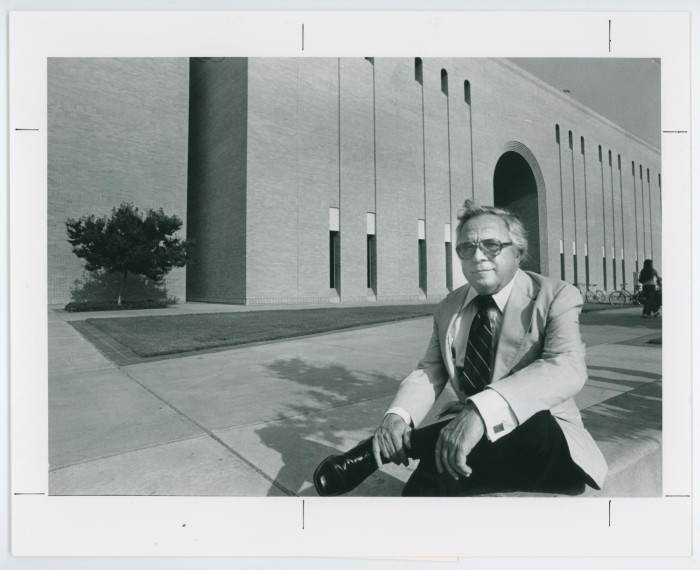 Black and white photograph of an older man wearing a suit and tie, sits posed on a step outside of a long brick building.