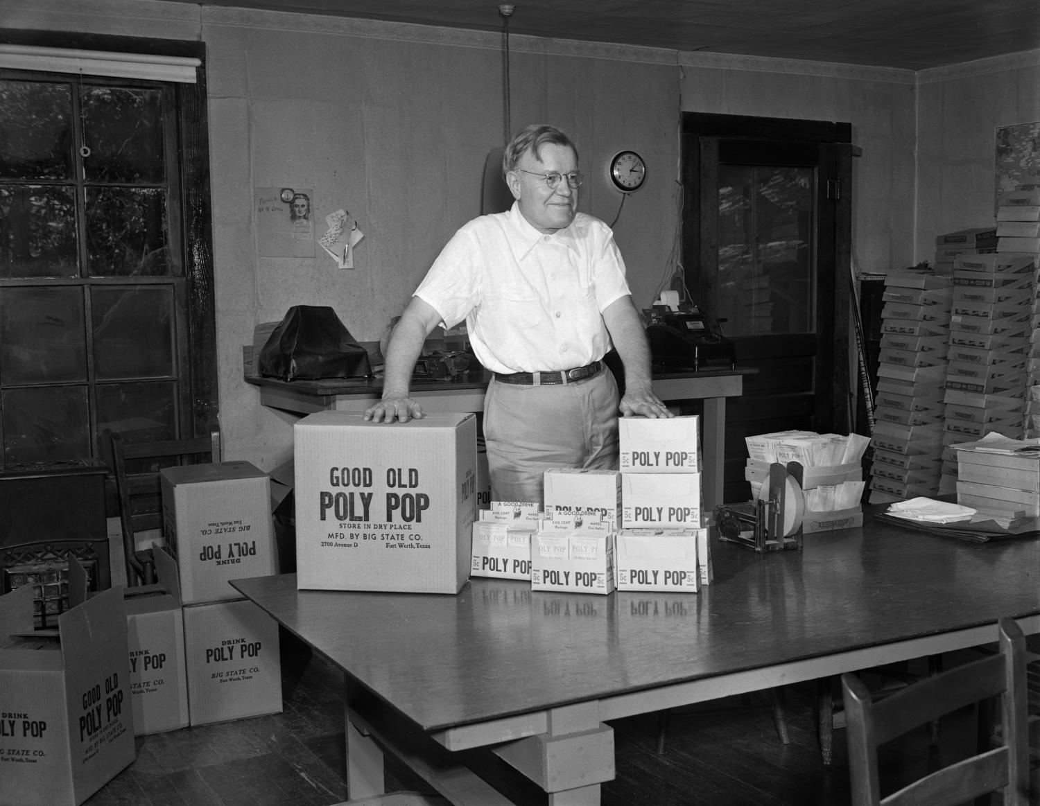 "Black and white photo of a white man standing behind a large table with many boxes that read ""Good Old Poly Pop."" He has his hands on two boxes and looks to the right with a smile. More boxes line the walls and are on the floor around him."