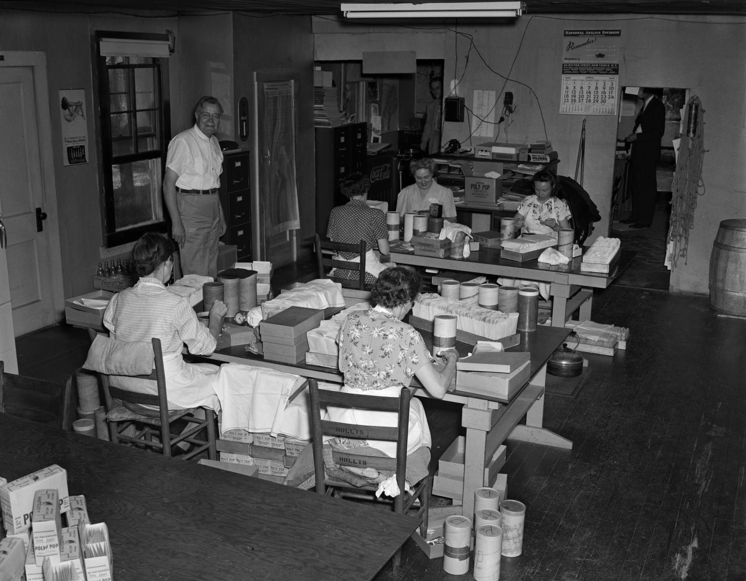 Black and white photo of five white women worked at two tables in a room. They have boxes and other materials on the tables and are seated looking down. A white man stands to the side of the tables and looks at the camera.