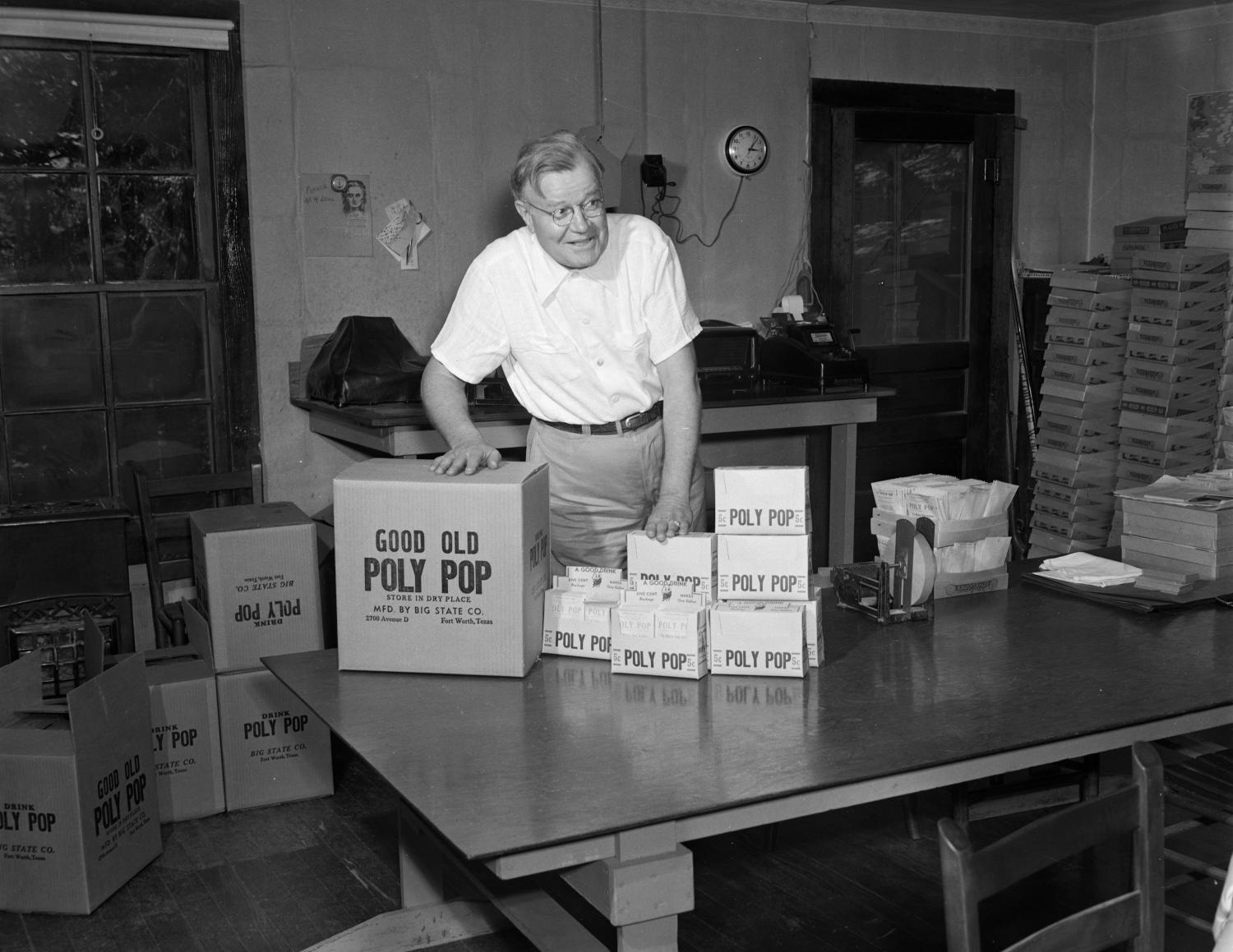 "Black and white photo of white man standing behind a large table with boxes that read ""Good Old Poly Pop."" He has his hands on two boxes and looks to the right with a smile. Boxes line the far wall, and are on the floor as well."