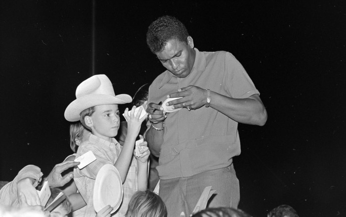 Black and white photo of a Black man signing autographs. A boy in a cowboy hat holds out a piece of paper, and other hands can be seen holding things out.