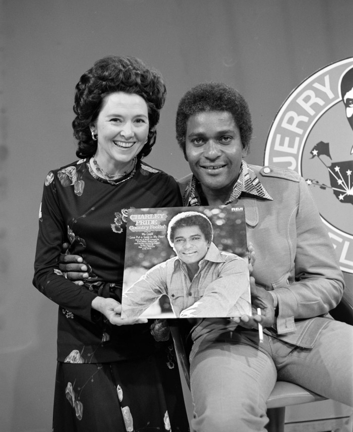 Black and white photo of a white woman next to a Black man, holding up a record cover with his photo. They smile at the camera.