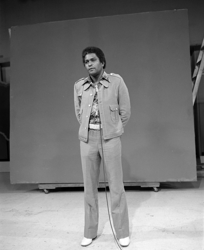 Black and white photo of a Black man standing in front of a blank backdrop. He wears a 1970s style leisure suite with patterned shirt.
