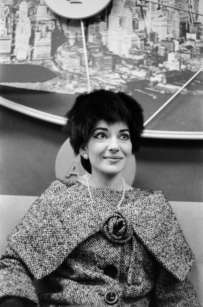 Black and white photo of white woman sitting in front of an image of Dallas. She wears a black fur hat, coat and pearls.